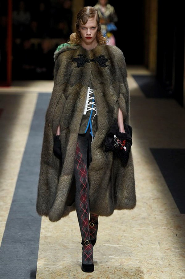 <strong>PRADA</strong><BR><BR> Fur was left natural and used to trim the sleeves of patchwork jackets, plaid capes and distressed black leather coats, both long and short. A midi sheered mink had a detachable hoodie—because luxury should be utilitarian, too. But the show-stopper was a hooded fur-and-argyle tights combo. With a model in slick hair and blood red lips, the entire look was wild and divine.