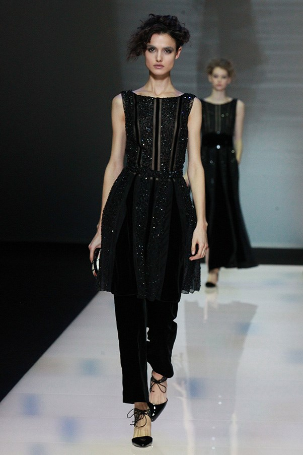 <strong>GIORGIO ARMANI</strong> <BR><BR> He toned down his evening looks from klieg-like Hollywood to rarefied cocktail attire. A tunic with black beads and carwash flaps topped black velvet pants and sophisticated sandals, while wide velvet belts held up curtains of pom-pom detailed gauze trapeze frocks.