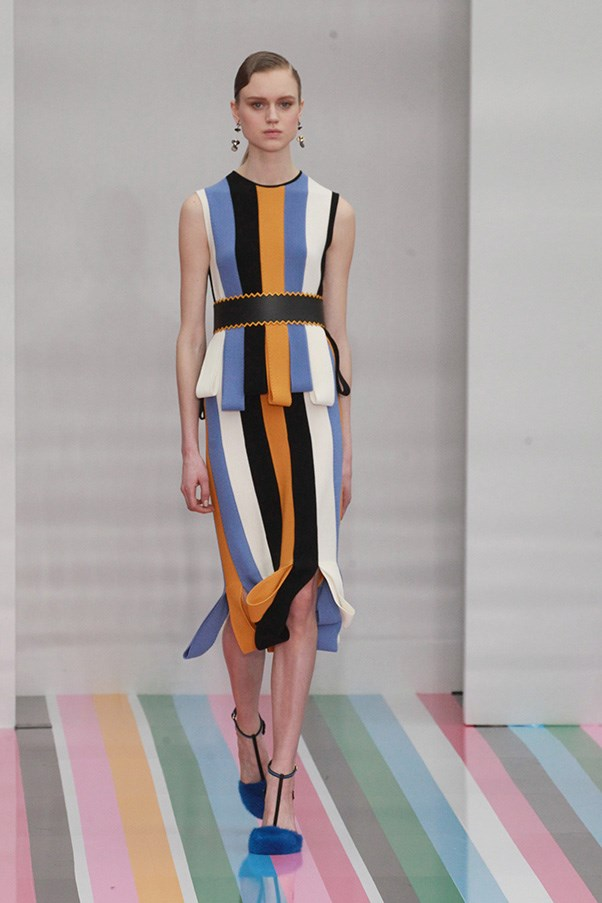 <strong>SALVATORE FERRAGAMO</strong> <BR><BR> Sticking to the stripes motif was not limiting, though. It forced him to get creative. He folded flaps of alternating colors in a tunic-and-pencil skirt combo, while in another, golden zippers provided graphic edge to a black tunic dress. A handful of all-white pieces featured tiers of micro pleats or, as seen on a refined coat, seamed panels with a tulip hem.