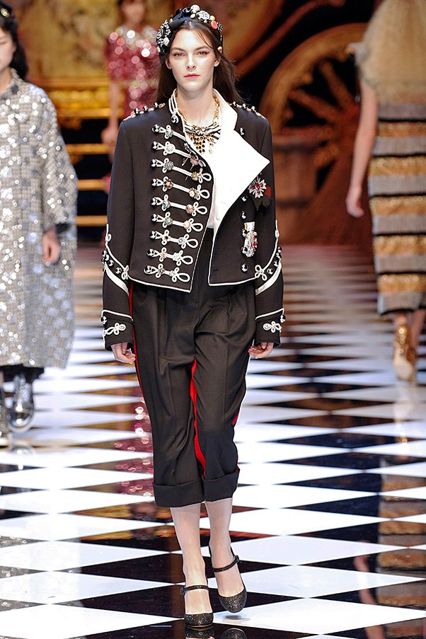 <strong>DOLCE & GABBANA</strong> <BR><BR> For every shimmering pale blue and shiny pink dress—either in a-line or cinch-waisted silhouettes—there was a military look festooned with ribbons and buttons, paired with cropped pants. The models all wore jeweled crowns, some with buttons and safety pins...because that's what a princess locked in a tower had to make do with, right?