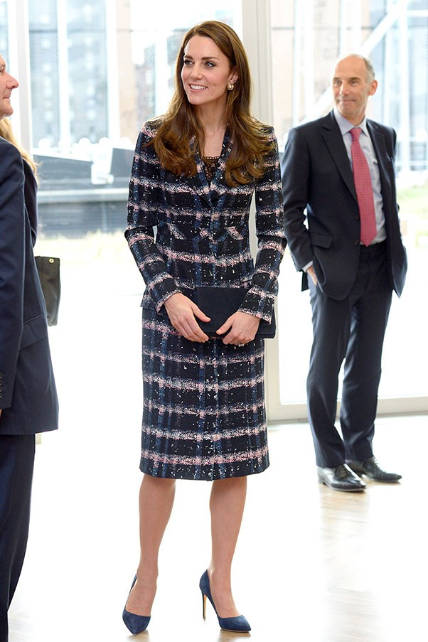 The Duchess visited the National Football Museum in Manchester, wearing a black, blue and pink plaid Erdem coat, paired with a navy blue clucth and suede blue heels.