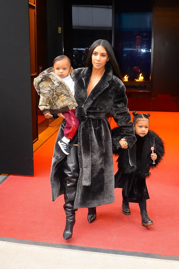 <strong>February 1st, 2017</strong><br><br> Kim stepped out for a family outing with her stylish children Saint and North, opting for a plush coat and thigh-high boots.