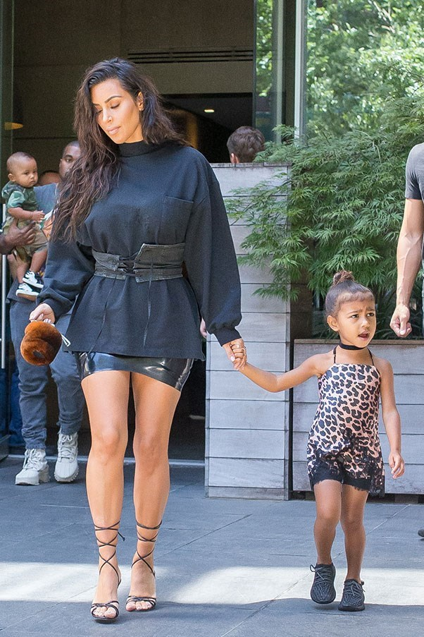<strong>August 29th, 2016</strong><br><br> Kim wore a Prada corset belt over an oversized white sweater and lace-up sandals while out with daughter North in New York City.