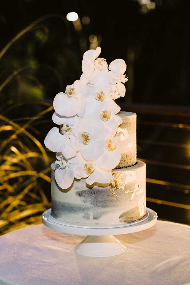 <strong>On the cake: </strong> <br><br> Our cake was two tiered, white and grey marble, with scattered gold leaf and orchids cascading down. The cake was styled to reflect other aspects of the wedding - we had gold foil on our invitations, marble name tags for the place settings and orchids in my bouquet and the table arrangements. The cake was salted caramel and white chocolate flavoured with buttercream.