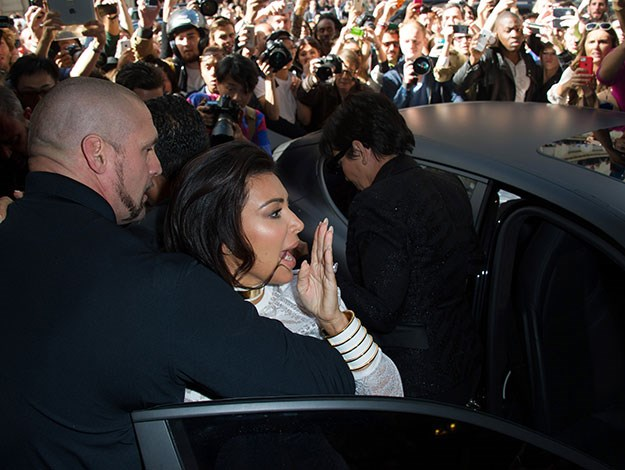 Kim, Kanye West and her mother Kris Jenner were caught in a crush of people and paparazzi as they arrived at the Balmain fashion show in Paris/