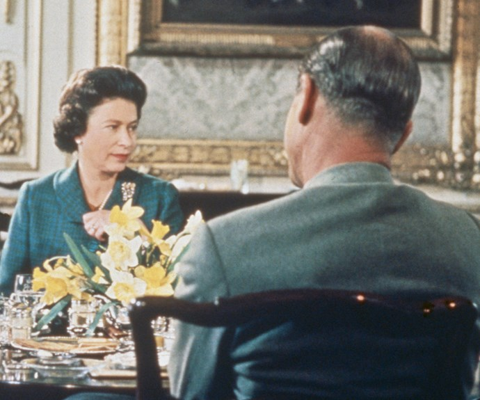 The Queen is photographed here wearing an emerald green, tartan ensemble.