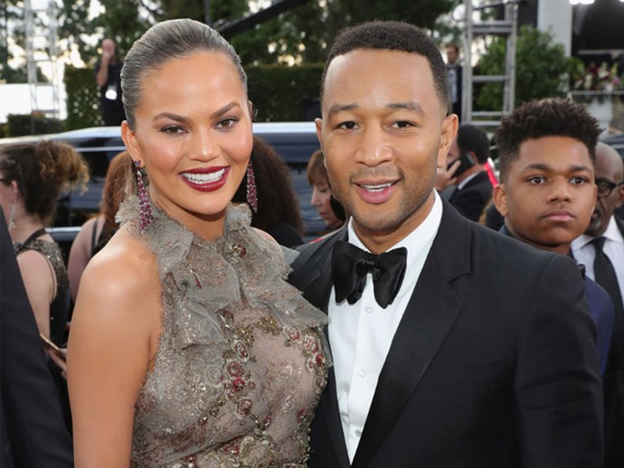Chrissy Teigen did her Golden Globes red carpet interview with Ryan Seacrest sitting like a queen