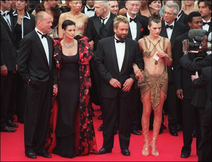 **BRUCE WILLIS, DEMI MOORE, LUC BESSON, AND MILLA JOVOVICH, 1997**  OMG, it's like you've never seen a woman wearing a gold chainmail loin cloth with a matching nipple harness, Bruce Willis?