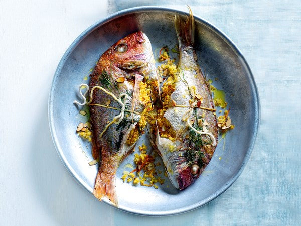 Tray-baked whole fish with citrus couscous stuffing
