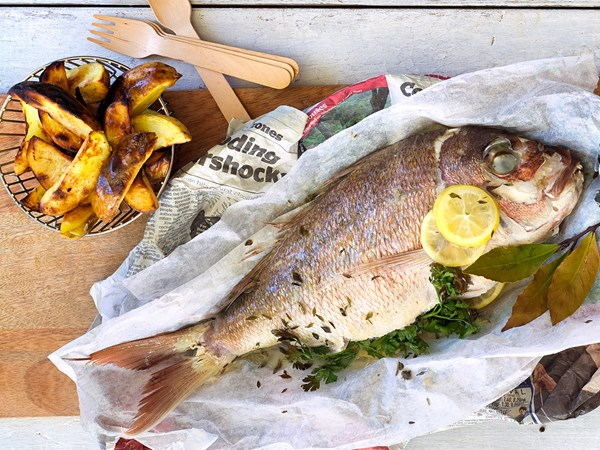 Whole paper-baked fish with potato skins and tartare