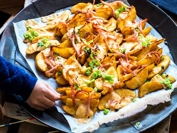 Loaded potato wedges with smoked cheese sauce and bacon