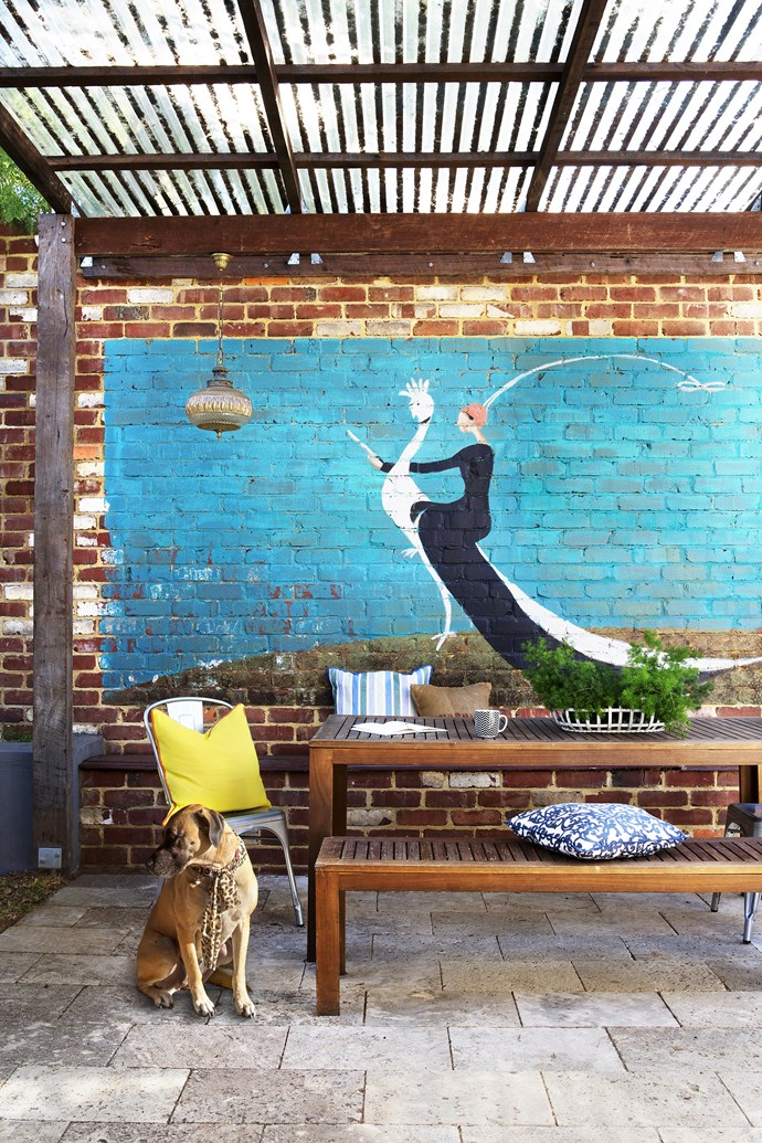 Ben constructed the pergola from recycled jarrah posts and beams; clear sheeting on its roof allows winter light into the house. Carla painted the vintage *Vogue* mural on the recycled brick wall to match the colours and tones of the interior.