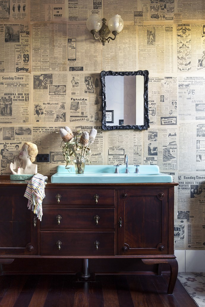 Newspapers found in the original home were upcycled into a one-off wallcovering. The vanity is made from an antique dresser, stained to match the kitchen cabinetry. The aqua enamel basin, sourced at a salvage yard, was one of the first items the couple found for the building project.