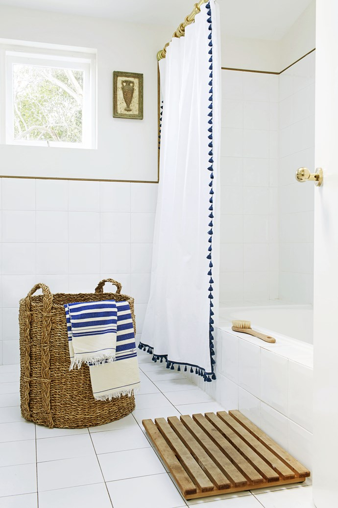 A bolt of blue, via towels and a fun pompom showerscreen that Heidi found in the US, lifts the white bathroom scheme.