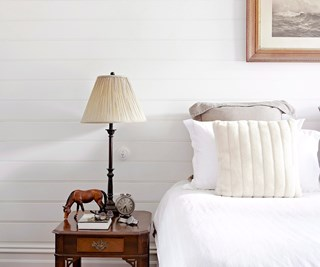 Bed with plain sheets and bedside table with lamp and horse figurine