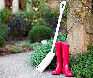 Red wellies and a white spade in the garden