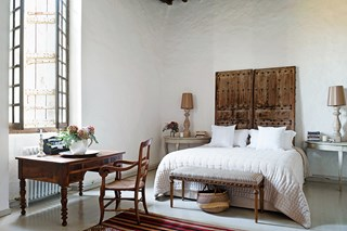 Bedroom with wooden furniture and white sheets