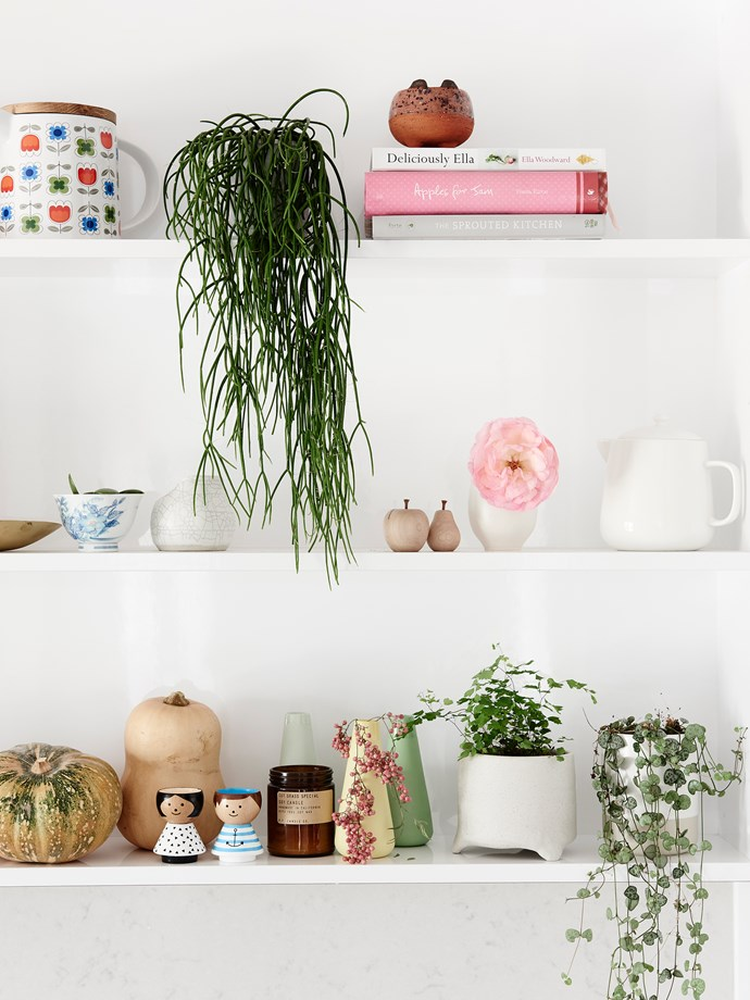Knick-knacks and pops of pink and green enliven and personalise the otherwise minimalist kitchen.
