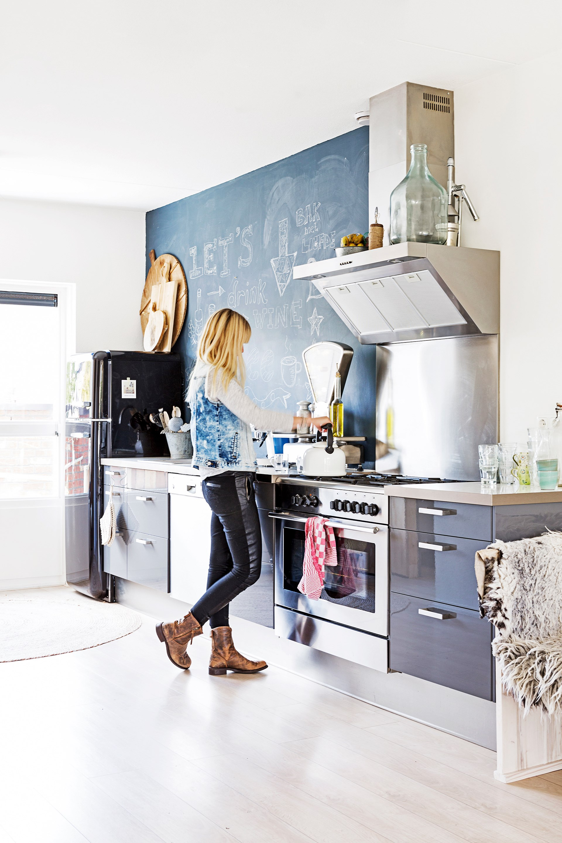 """Marieke makes a cuppa in her industrial-style [Ikea](http://www.ikea.com.au/?utm_campaign=supplier/ target=""""_blank"""") kitchen. Fun notes and recipes are written on the chalkboard wall."""