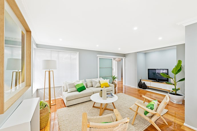 **AFTER:** The new-look living area is fresh and clean, with simple and stylish furniture chosen to reflect the beachy location. The original bar area has been converted into a TV alcove. The chandelier has been replaced with modern downlighting.