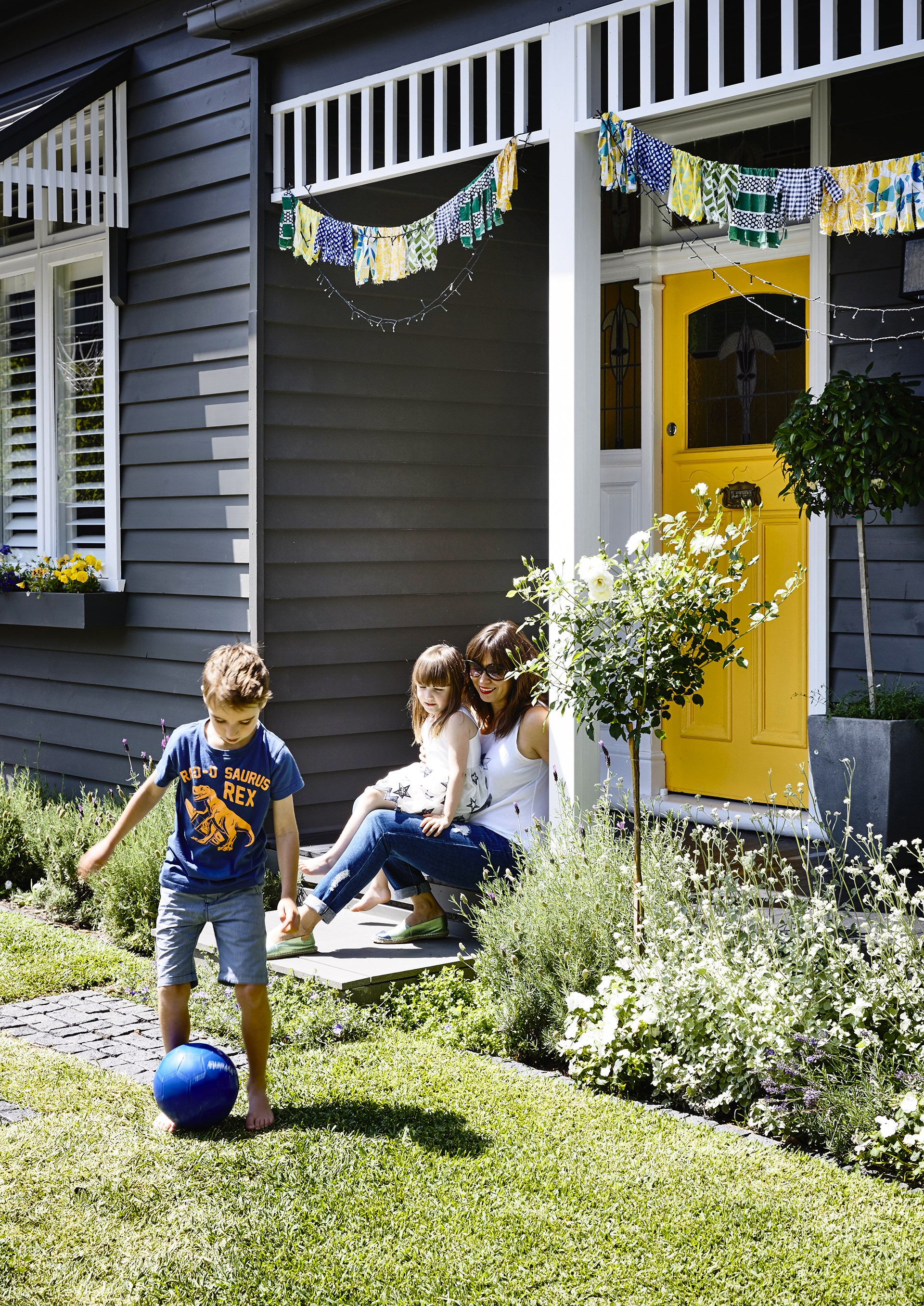 Marissa chose the bright yellow shade for the front door to draw the eye and add a sense of fun to their home's façade. The front garden's feature plants include 'Iceberg' rose and Licorice plant (*Helichrysum petiolare*).