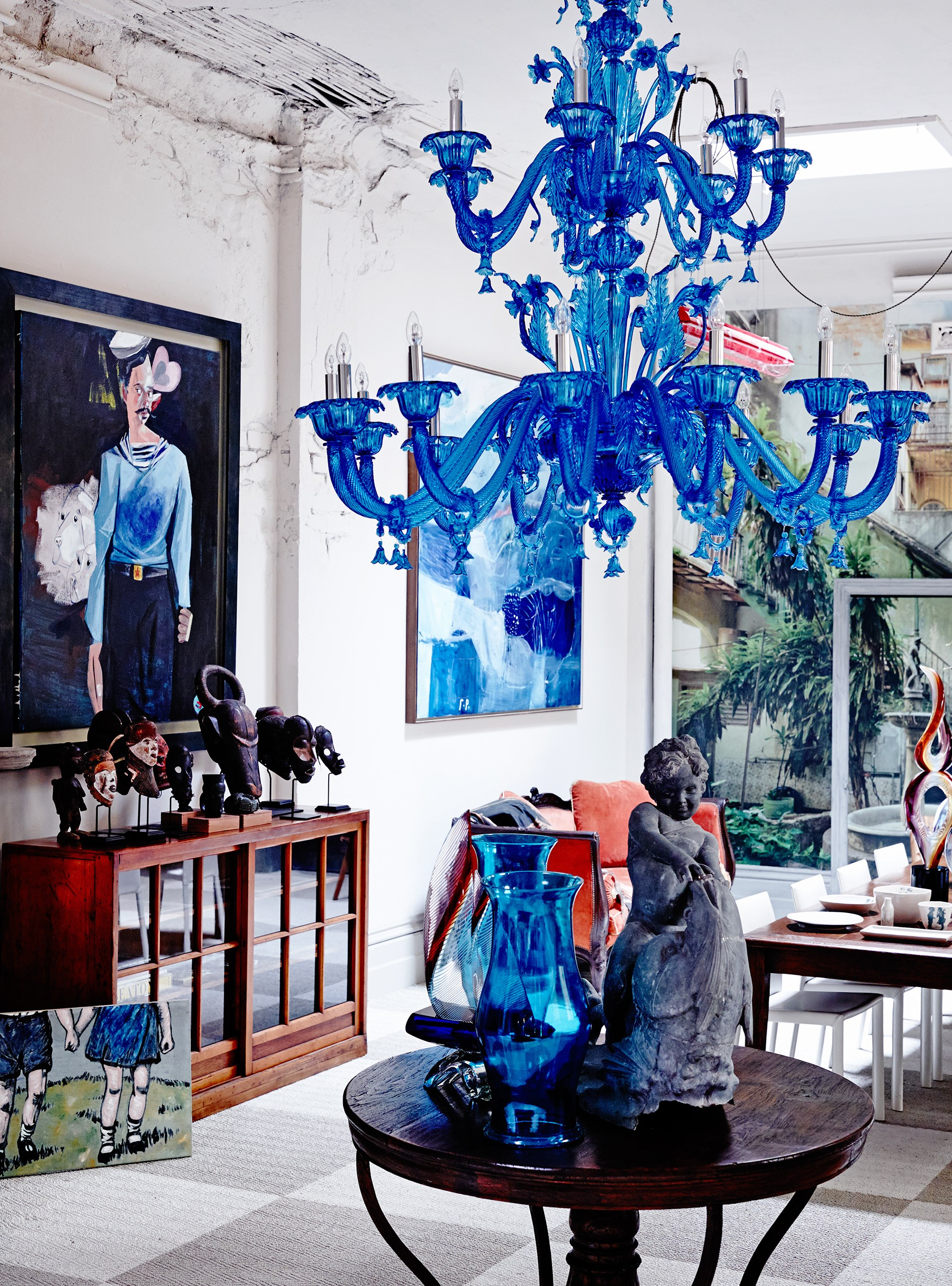 A blue Murano glass chandelier, mid-century sculptures from Ghana, a Japanese university cabinet and paintings by David Bromley (on floor), McLean Edwards and George Raftopoulos.