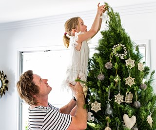 Father and daughter put star atop Christmas tree
