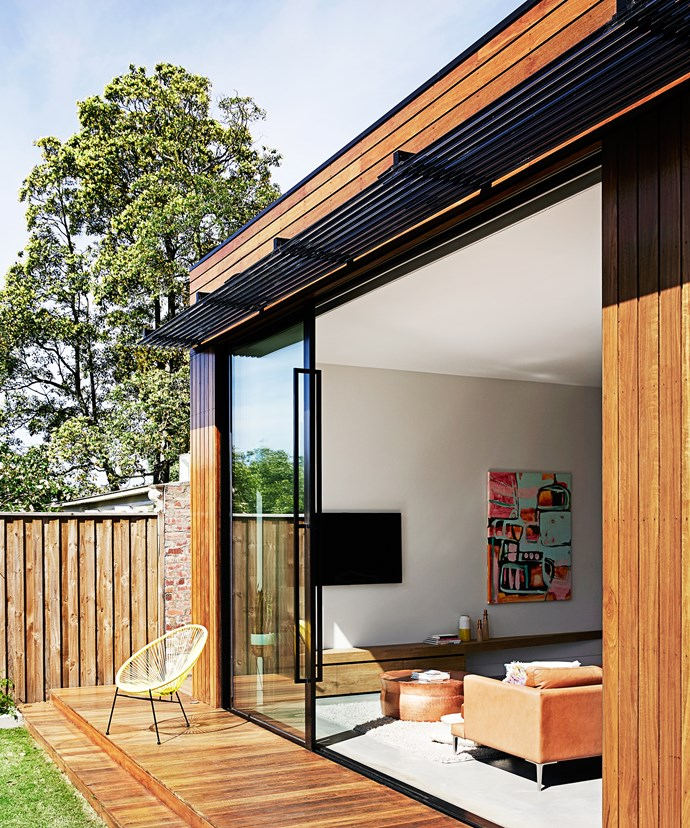 Floor-to-ceiling double-glazed sliding doors open onto the deck to give the open-plan living area an indoor-outdoor vibe. Custom black powdercoated louvres provide some shade.