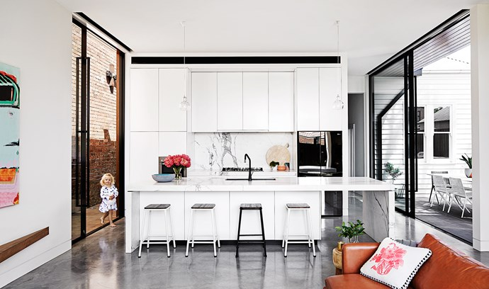 """Johanna chose crisp white for the kitchen cabinetry. """"It's classic and will never date,"""" she says. It's complemented by black accessories such as the mirrored LG fridge. A Calacatta marble splashback and matching benchtop add a luxe feel to the modern space. Bulb pendant lights from [Great Dane Furniture](http://www.greatdanefurniture.com/?utm_campaign=supplier/