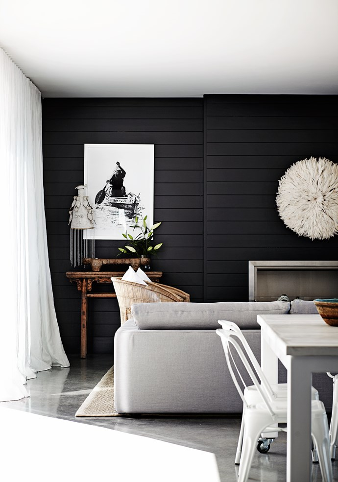 """The dark feature wall – painted in Porter's Paints """"Van Helsing"""" – helps define the living area and provides a stunning contrast to the light palette. """"It creates a different area to enjoy in the house,"""" Eduardo says."""
