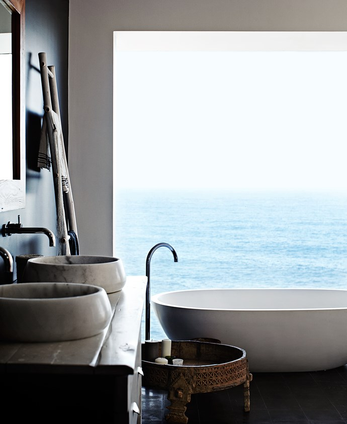 The Apaiser stone bath in the master bedroom ensuite is positioned in the best spot to take in the magnificent ocean view. The bath, along with the basins that were bought as one-offs from Indigo Tile Design, add an organic simplicity to the space. Haughey Group made the timber vanity.