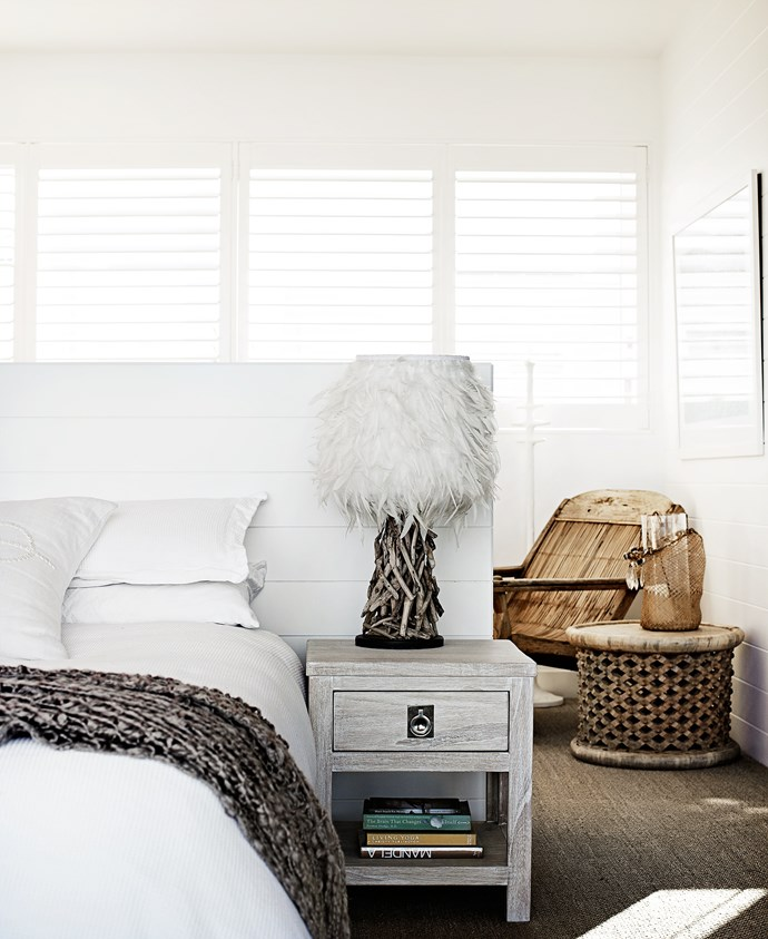 """The simple white palette with natural textures continues in the master bedroom. A feather and driftwood lamp, bought in Bryon Bay, whitewashed Cancun bedside tables from [Freedom](http://www.freedom.com.au/ target=""""_blank"""") and a sisal carpet add to the calming, beachy-retreat vibe."""