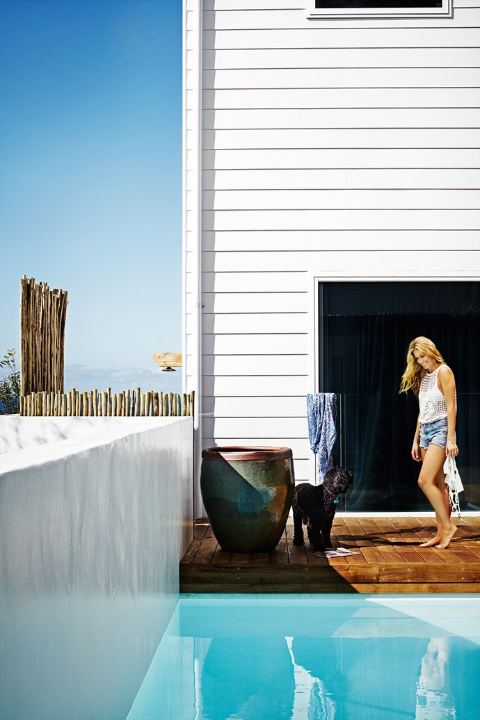 """""""Weatherboard was chosen to create the beach-house look the clients wanted,"""" Eduardo says. Latte poles, used here in a fence, are repeated in other outdoor areas, creating a link. A white concrete wall at the end of the pool fits with the serene palette."""