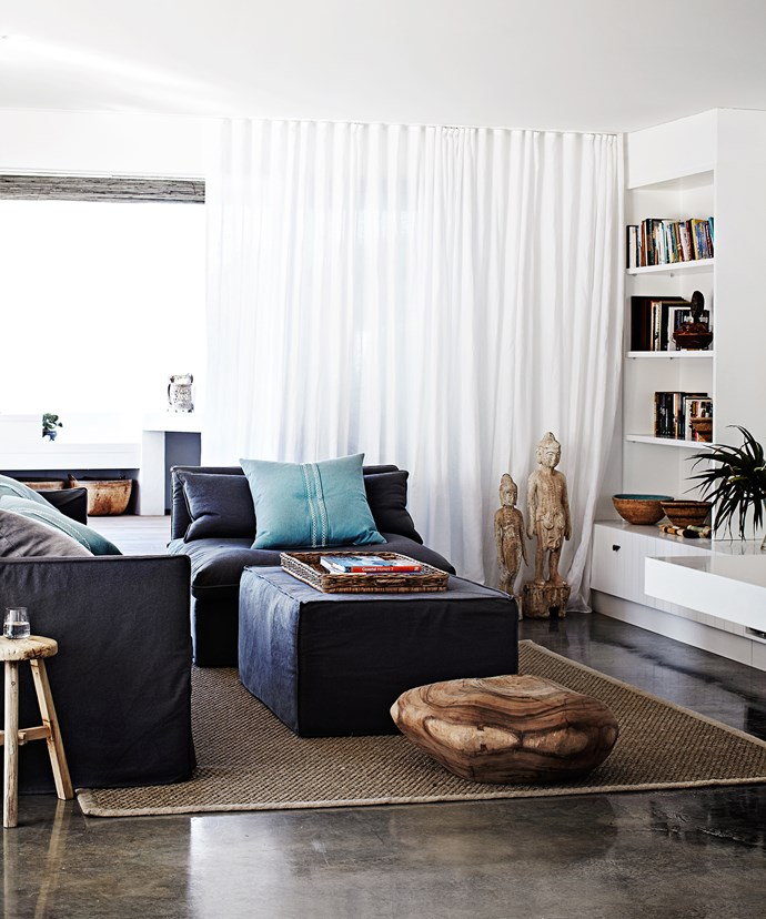 """In the open-plan casual family area, layers of textural interest have been added through accessories, such as linen slip covers on the sofas, a large carved piece of timber on the floor and a sisal rug from the [Natural Floorcovering Centre](http://www.naturalfloor.com.au/ target=""""_blank""""). The stone statues are by Zimbabwean sculptor Dominic Benhura."""