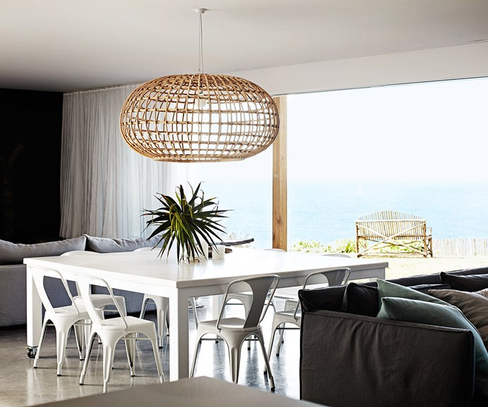 """""""You can either open up the home to the elements, or close it up for a lovely, cosy space,"""" the homeowners say of the casual dining area. The sheer linen curtains add a soft elegance to the space and diffuse the light beautifully."""