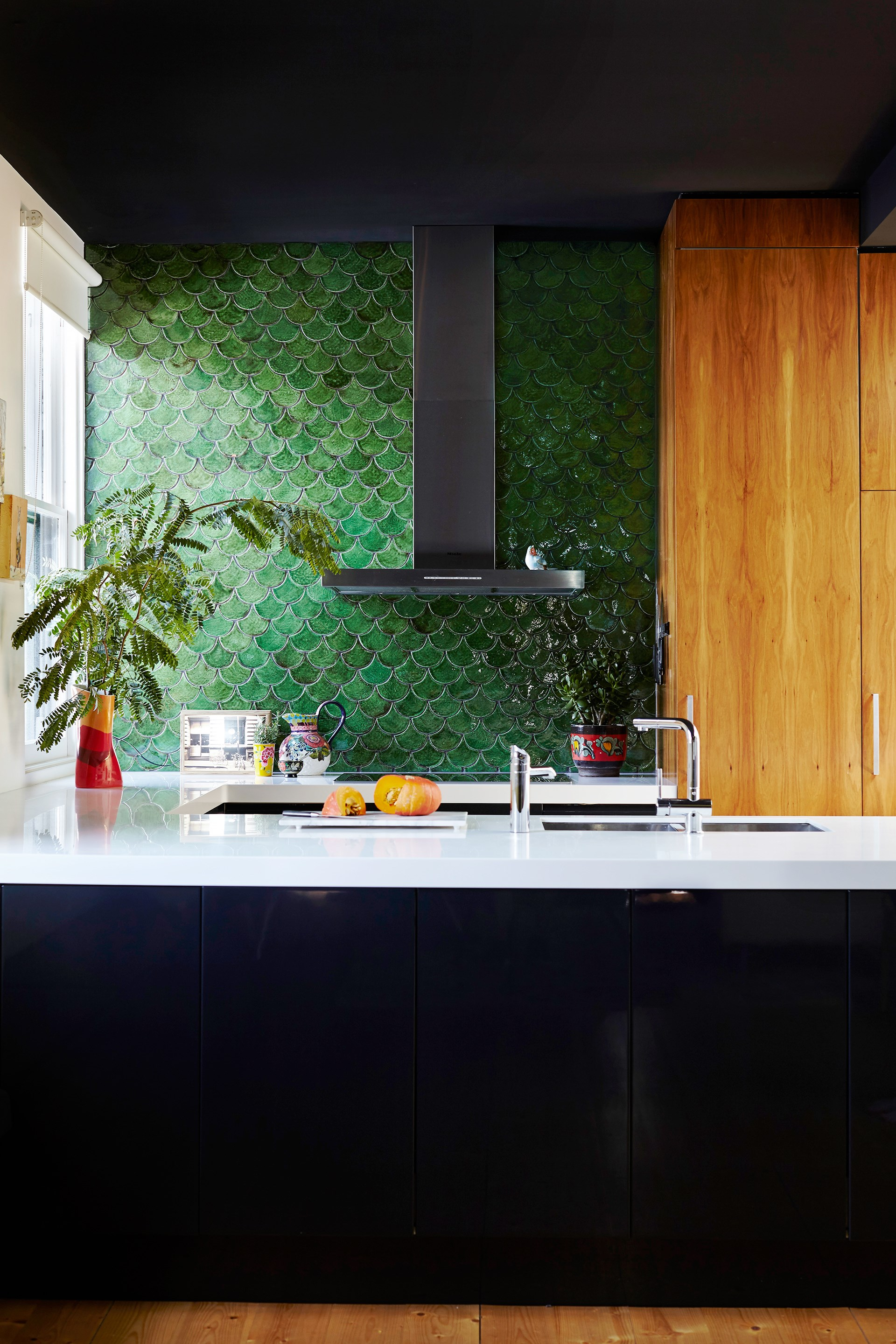"""Olive-green fishscale-patterned tiles add character to the contemporary kitchen in this [Victorian home](http://www.homestolove.com.au/grand-victorian-home-gets-a-colourful-personality-3642