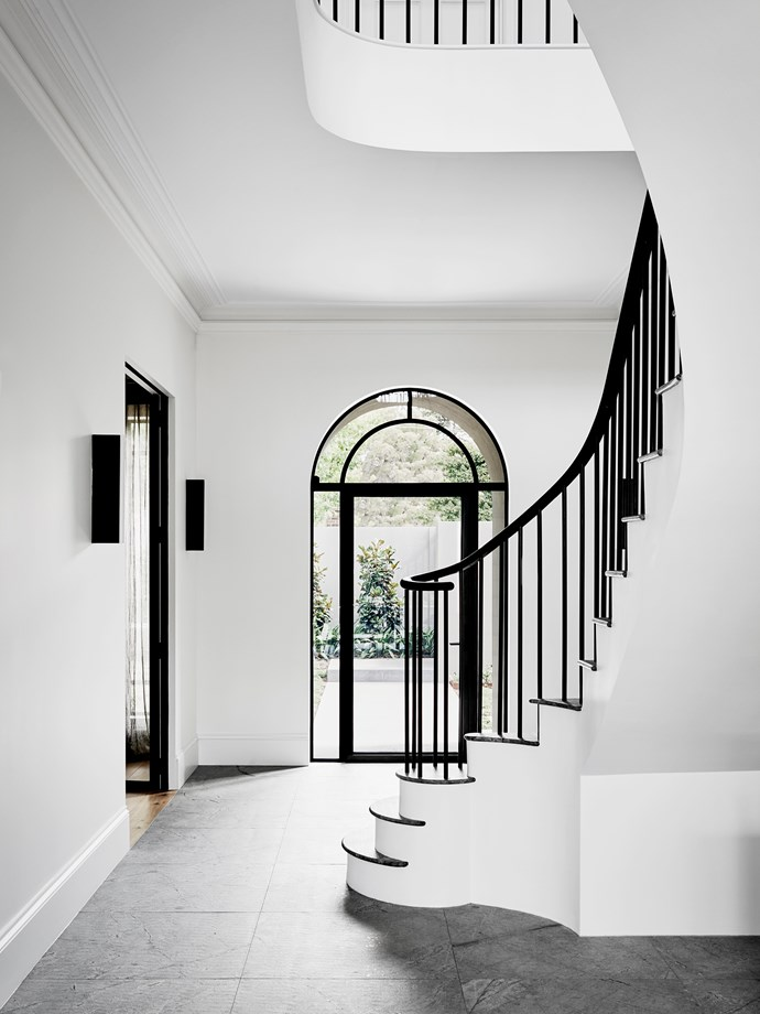"The entryway is dramatic both for its expansive void and sculptural staircase. The space was stripped of its tiled Carrara marble and replaced with 'Blue Moon' granite with an exfoliated finish from [CDK Stone](http://www.cdkstone.com.au/?utm_campaign=supplier/|target=""_blank"")."
