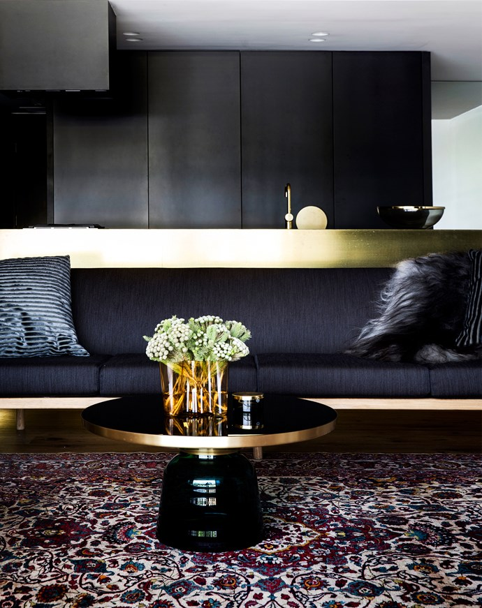 """A luxurious brass island in the kitchen contrasts with the darker joinery panelling built by [Connect Constructions](http://connectconstructions.com.au/