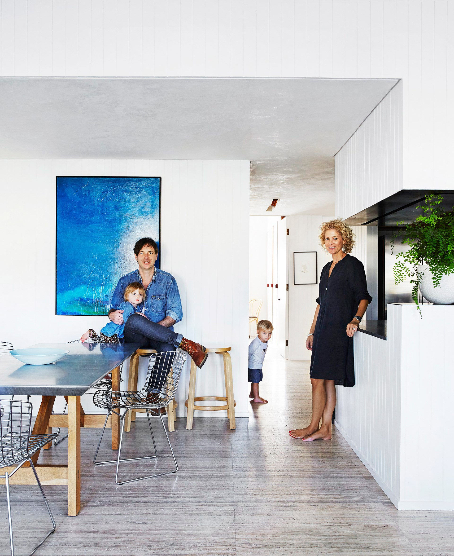 "Andrew and wife Georgie with twins Leni and Beckett in their transformed space. New 2.9m-high ceilings, walls and a floor were added, as well as recessed lighting, to an area that used to have grey carpet, rounded walls and [pendant lighting](http://www.homestolove.com.au/14-pendant-lights-that-pack-a-punch-2989|target=""_blank""). Andrew created the artwork he's in front of as well as the zinc-topped dining table. The stools are [Artec](http://www.artek.fi/products/chairs/128