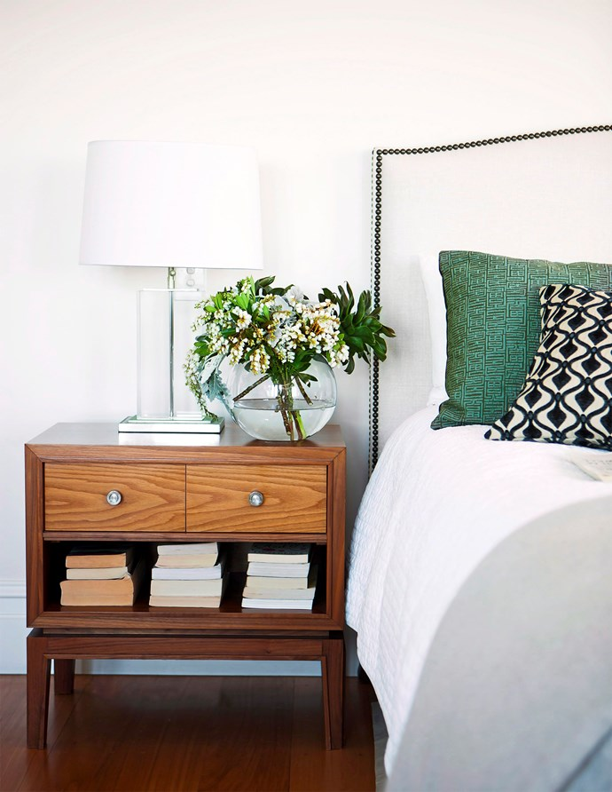 Style up your bedside with a statement lamp and a vase of flowers.