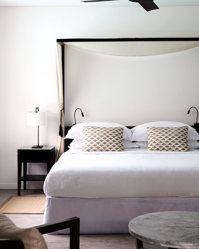 The guest bedrooms adopt a more minimal aesthetic, with crisp muted textiles and breezy canopied beds. With the addition of driftwood timber-tiled floors and natural wood furnishings, it's contemporary coastal chic at its finest.