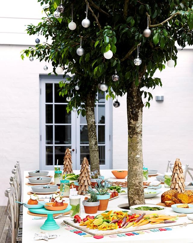 If you're dining formally outside, consider what natural features you can add a festive touch to. Trees make the perfect place to hang Christmas baubles and you can display wreaths or lights on walls and on the side of your house, too. *Photography: Nick Scott / bauersyndication.com.au*