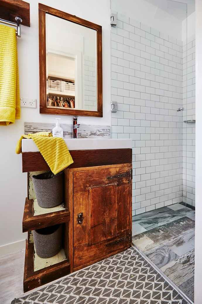 The DIY projects continue in the bathroom, where Scott transformed an old ice box (picked up for just $20) into a vanity by adding on a sink, removing the interior shelves and building a few new ones out of recycled timber on the side.
