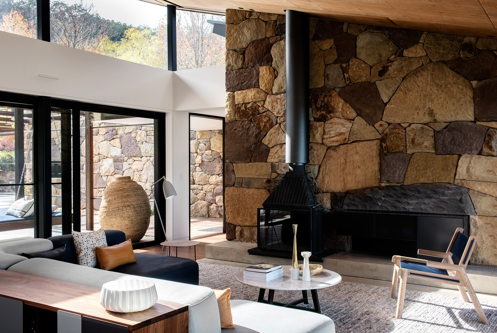 """The stone was quarried on site with bulldozers dispatched upwards to harvest """"car-sized chunks that had fallen off the escarpment"""", explains Ben of the beautifully crafted dry-stone walls by J&J Stonewall Constructions that back the pods and define the living room and outdoor dining spaces."""