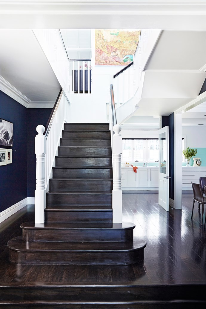 By removing three walls, Anna Maria ensured the home's spaces flow without interruption. The walls are painted in cocooning indigo, which frames a cluster of family photos (at left). Artwork on stairwell by Angelina George.