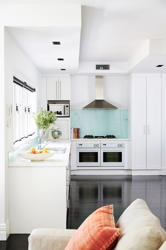 """The kitchen's openness is accentuated by soft white joinery in Dulux Lexicon Quarter. Anna Maria stained the existing brushbox floors in 80-per-cent Japan Black """"to take out the red, but keep the grain""""."""