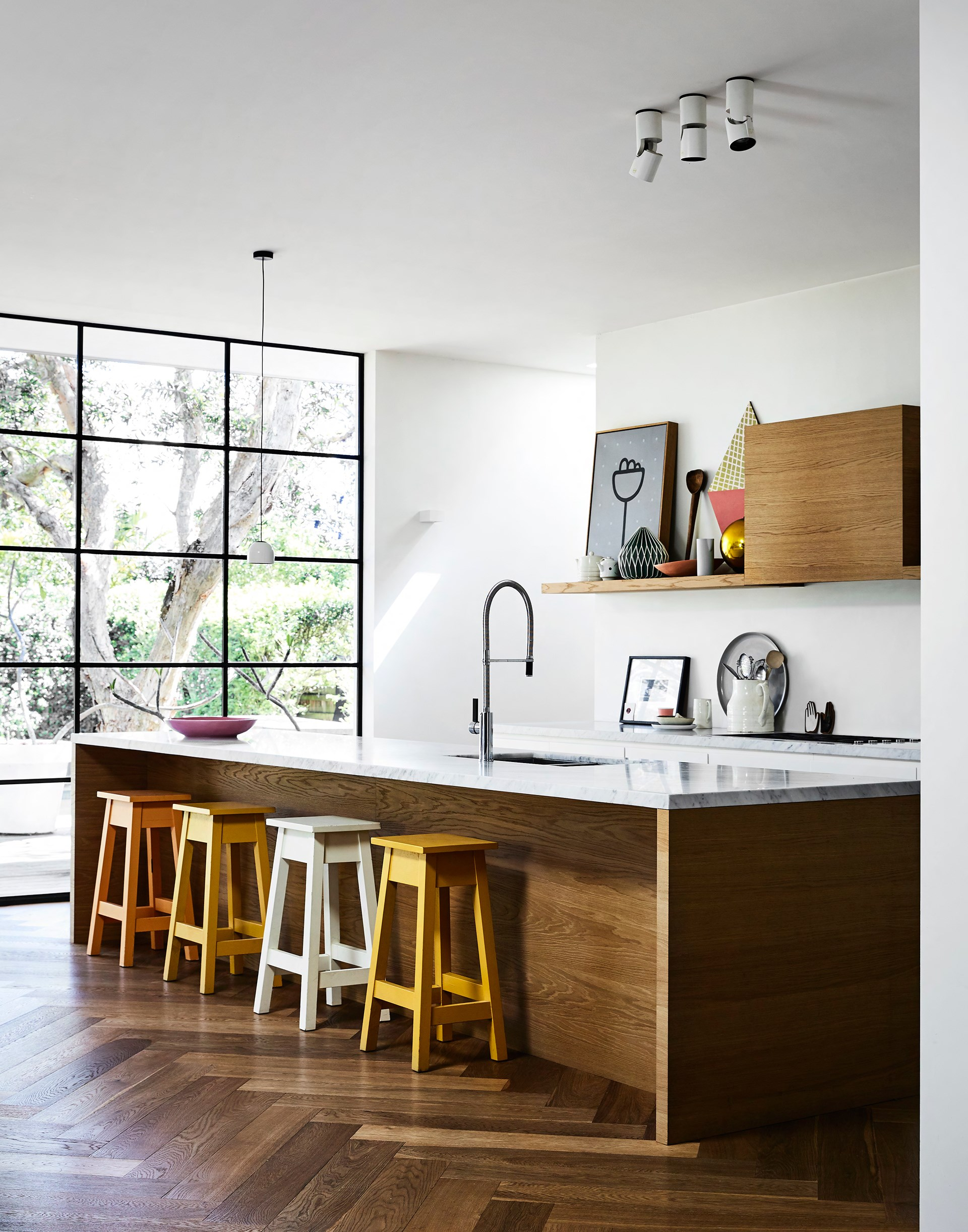 """The kitchen island and shelving are in a timber veneer by [George Fethers & Co.](http://gfethers.com.au/) """"Tina, our interior designer, spent a long while sourcing a match for the floors,"""" Rachel says. The benchtop is Carrara marble from [SNB Stone](http://www.snb-stone.com/). Four stools from [Mark Tuckey](http://www.marktuckey.com.au/) add subtle earthy tones."""