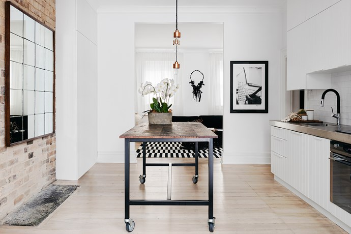 The kitchen features Smeg appliances and an artwork by Andy Summers. The client's island bench was retained and the original floorboards were limewashed.