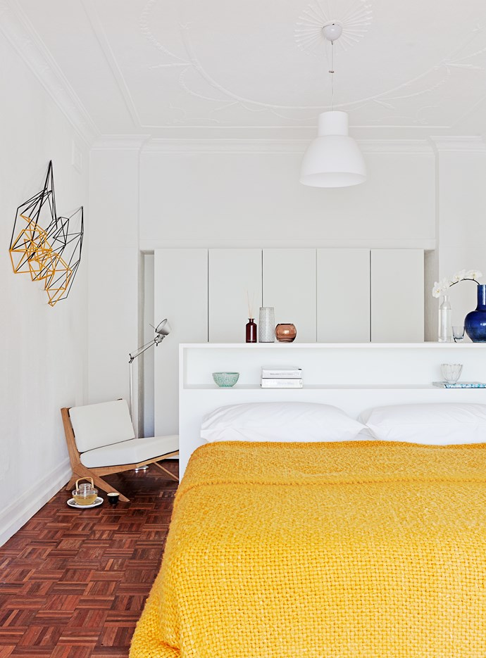 Like the rest of the home, the master bedroom has a simple palette. Here, the colour comes by way of a yellow bedspread and a Dion Horstmans sculpture.
