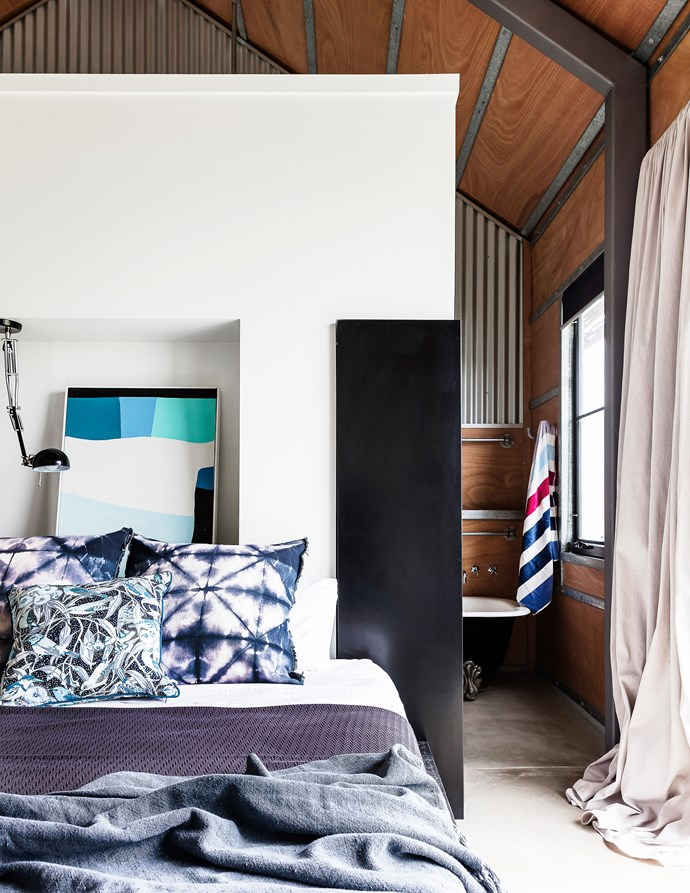 Affixed to the recess above the bed, an Ikea Forså desk lamp becomes an effective overhead light. Lockers are built into either end of the bedhead wall for extra storage.